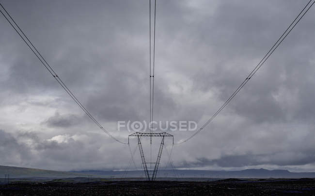 Power cables running to pylon against cloudy sky — Stock Photo