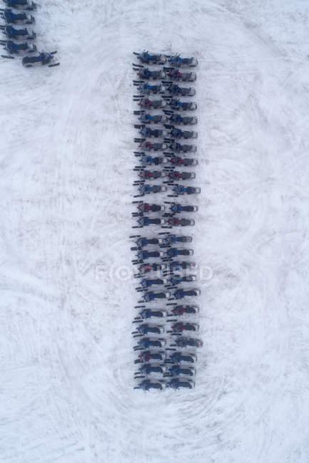 Вид с воздуха на снегоходы, припаркованные рядами на снегу — стоковое фото