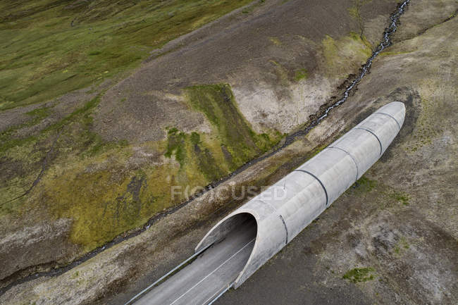 Drone view of tunnel through hilly landscape — Stock Photo