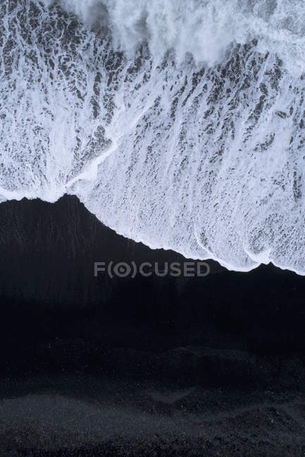 Aerial view of surfing wave on shore at beach with black sand — Stock Photo
