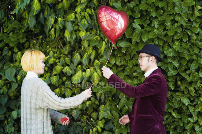 Side view of young couple holding heart shape balloon against plants at park — Stock Photo