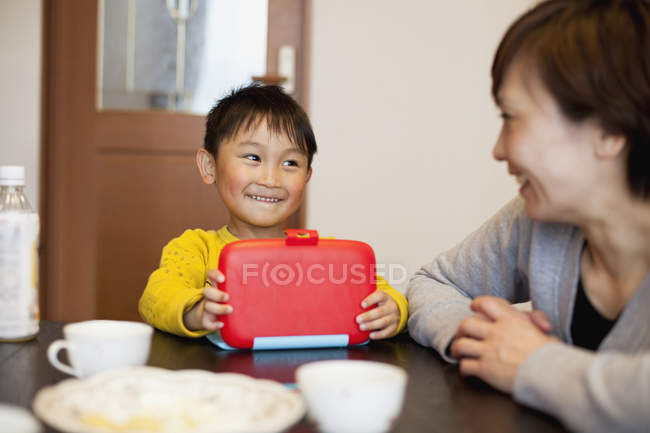 Smiling boy with lunch box looking at mother in house — Stock Photo
