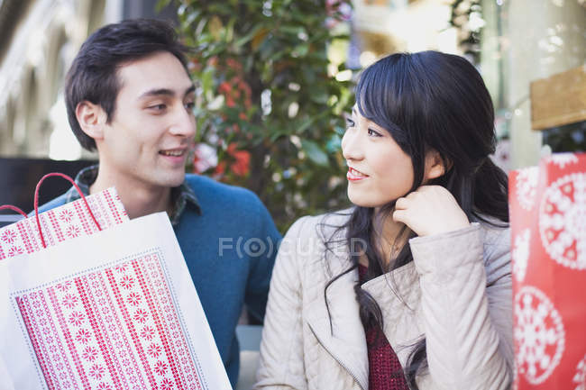 Loving young couple with shopping bags looking at each other — Stock Photo