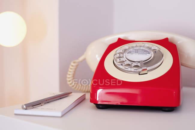 Червоний телефон з щоденник і перо на столі будинку — стокове фото