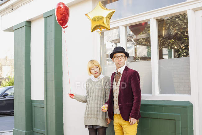 Young couple holding balloons and looking away at walkside — Stock Photo