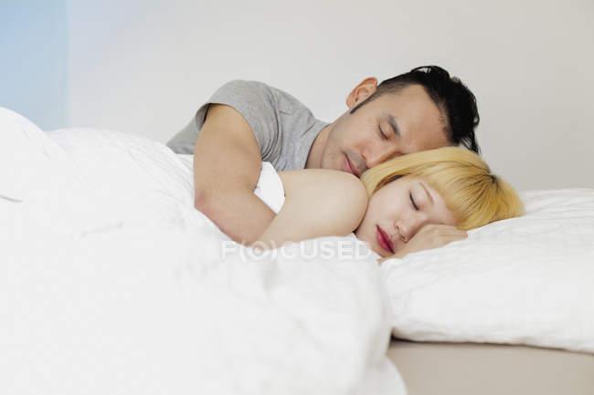 Молодая пара, спал на кровати у себя дома — стоковое фото