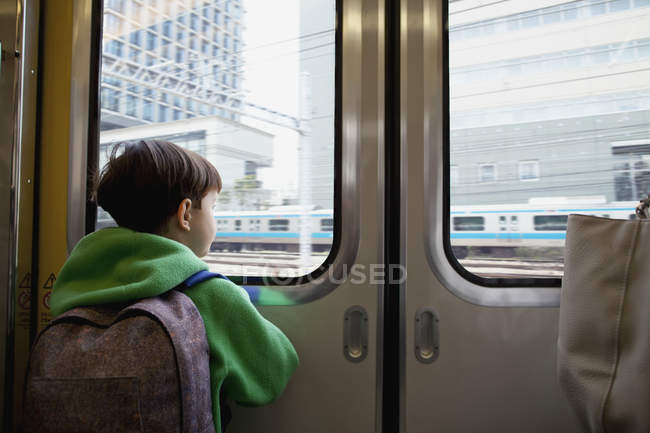 Rear view of boy looking through closed door while traveling in train — Stock Photo