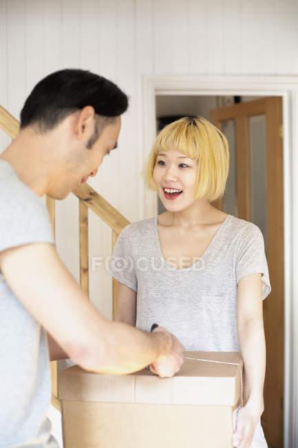 Улыбающаяся женщина смотрит на мужчину, несущего коробку во время переезда — стоковое фото