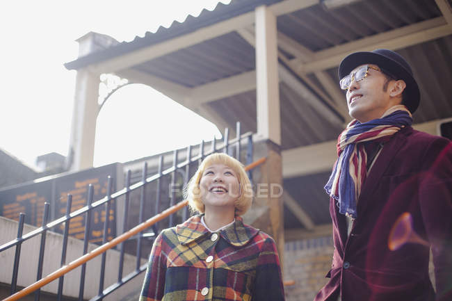 Smiling couple wearing autumn outfit standing against house — Stock Photo