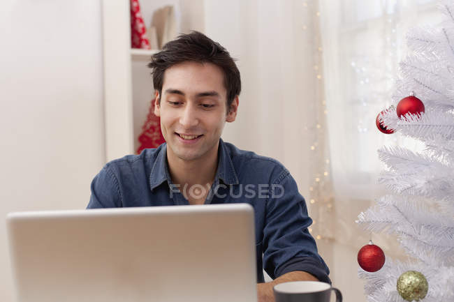 Smiling young man sitting by artificial Christmas tree and browsing laptop — Stock Photo