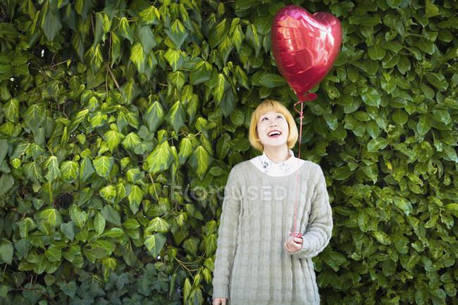 Mujer joven sonriente sosteniendo globo en forma de corazón mientras está de pie contra las plantas - foto de stock