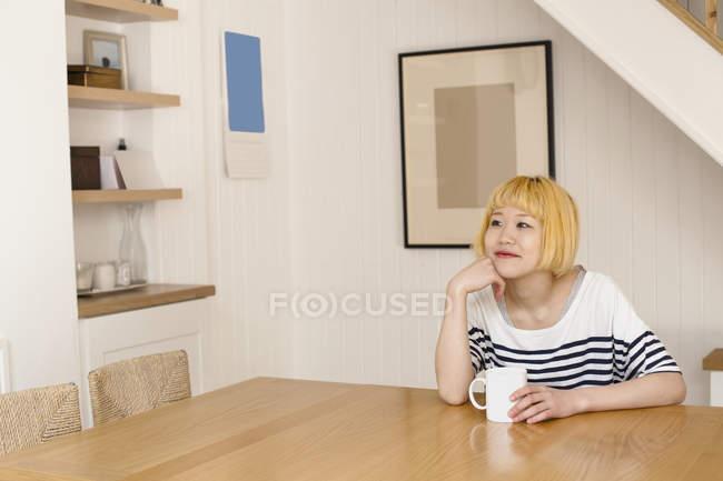 Мечтательная улыбающаяся женщина, сидящая за столом с кофе — стоковое фото