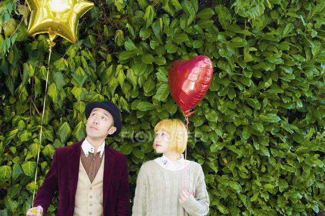 Couple looking at balloon while standing against plants — Stock Photo