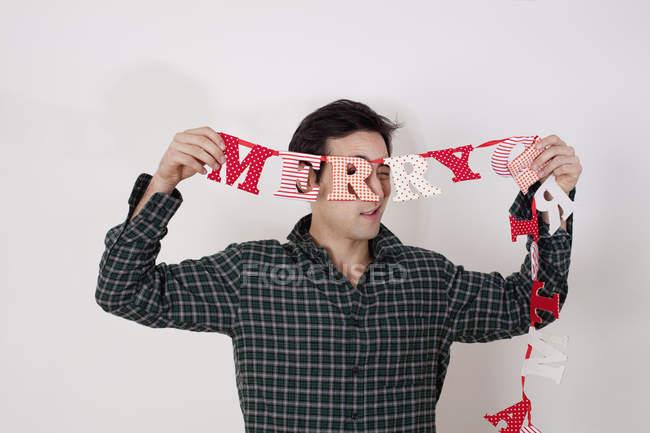 Uomo che tiene della stamina buon Natale mentre levandosi in piedi su sfondo bianco — Foto stock