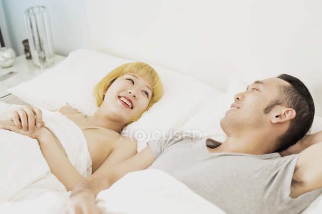 Jovem casal deitado na cama em casa a sorrir — Fotografia de Stock