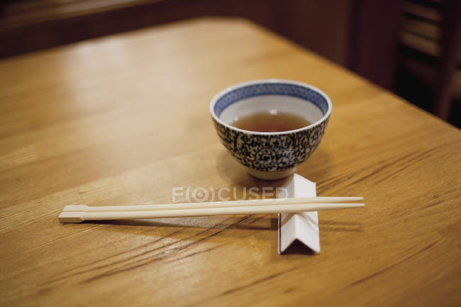 Still life of chopsticks and bowl on wooden table — Stock Photo