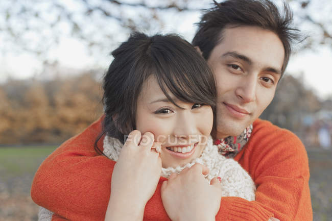Smiling young couple embracing in park during winter — Stock Photo
