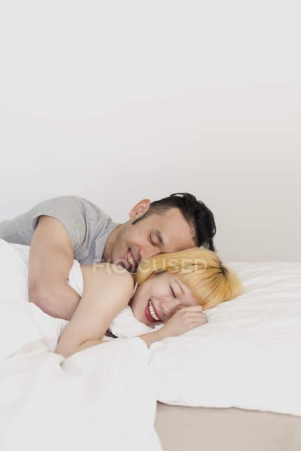 Sonrisa amorosa pareja abrazándose en la cama con los ojos cerrados - foto de stock