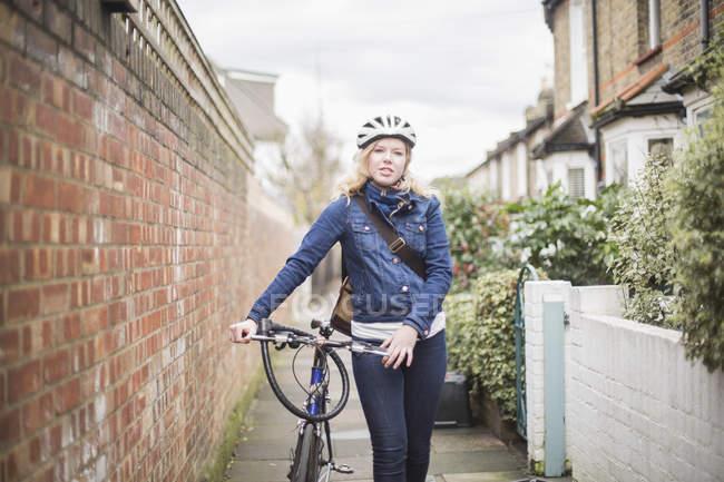Porträt einer jungen Frau, die mit dem Fahrrad auf dem Fußweg an der Mauer geht — Stockfoto