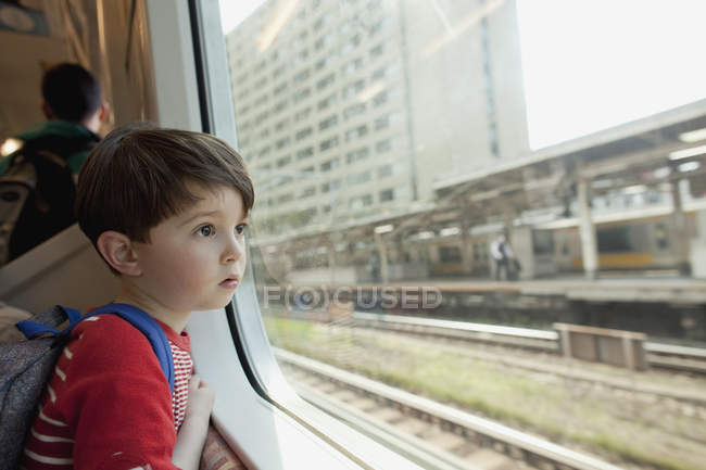 Curious boy looking through glass window while traveling in train — Stock Photo