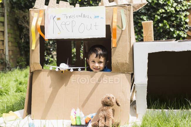 Portrait de garçon mignon avec des jouets regardant hors de la maison de jeux en carton — Photo de stock