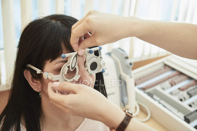Cropped image of optometrist examining woman's vision at clinic — Stock Photo