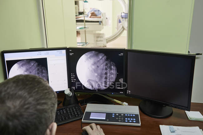 Overhead view of doctor looking at medical x-rays on computer in hospital — Stock Photo