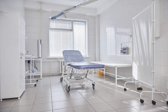 Camilla del hospital por ventana en sala vacía - foto de stock