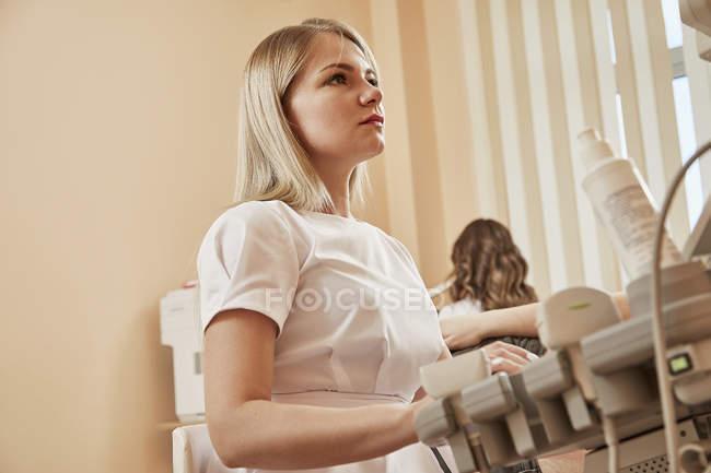 Медсестра, с помощью мониторинга оборудования во время лечения в больнице — стоковое фото