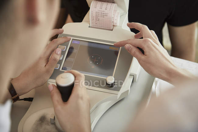 Nurses using machinery while examining patient during eye test at hospital — Stock Photo
