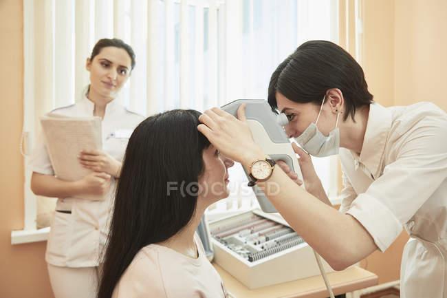 Медсестра, глядя на окулист, изучения женского пациента в больнице — стоковое фото