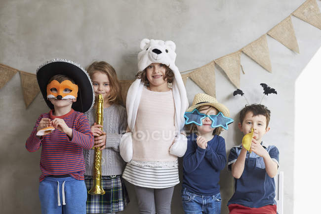 Smiling children with props standing against wall at preschool — Stock Photo