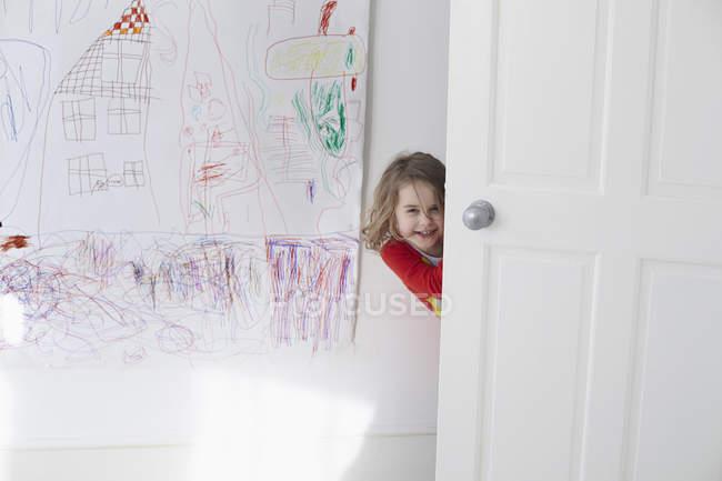 Retrato de menina alegre, escondendo-se atrás da porta contra o desenho na parede — Fotografia de Stock