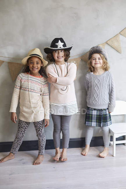 Full length of smiling friends standing against gray wall — Stock Photo
