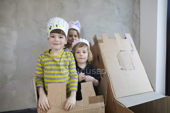 Friends wearing paper crowns standing with cardboard boxes against wall — Stock Photo