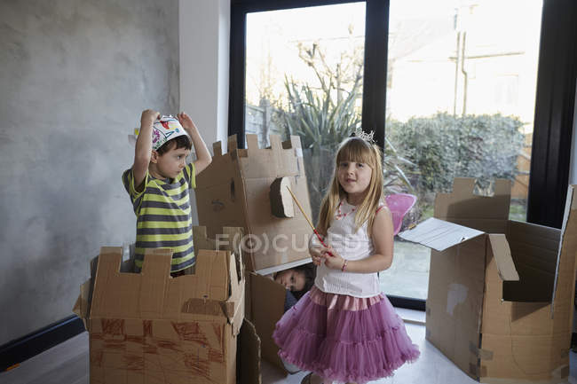 Children wearing costume playing with cardboard boxes against window — Stock Photo