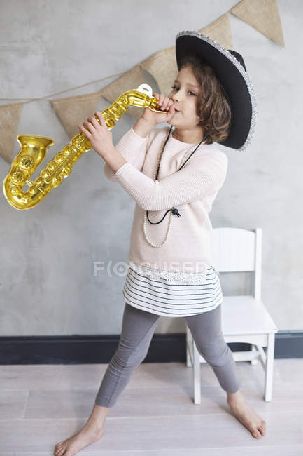 Full length of playful girl with prop trumpet standing by chair against wall — Stock Photo
