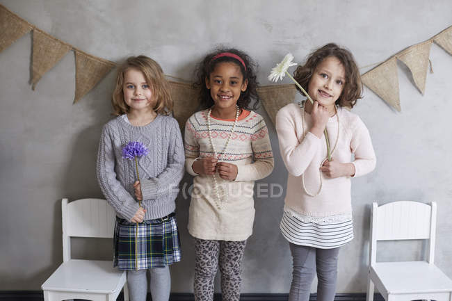 Full length of smiling friends with flower standing against gray wall — Stock Photo