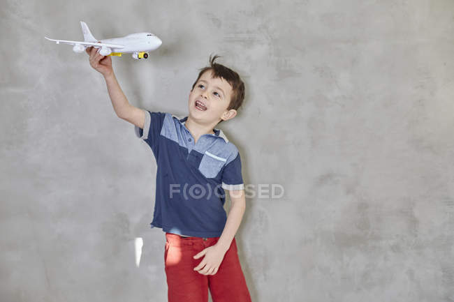 Boy playing with model airplane by gray wall — Stock Photo