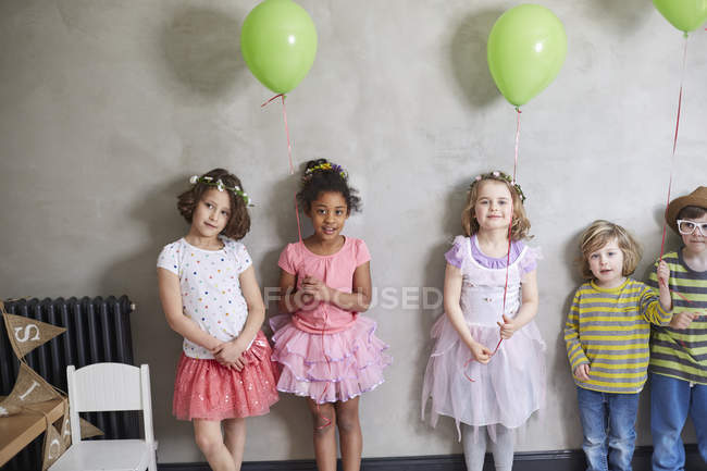 Portrait of girls and boys with green balloons standing against wall — Stock Photo