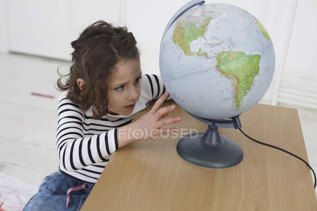 Fille explorer globe sur la table à l'école maternelle — Photo de stock