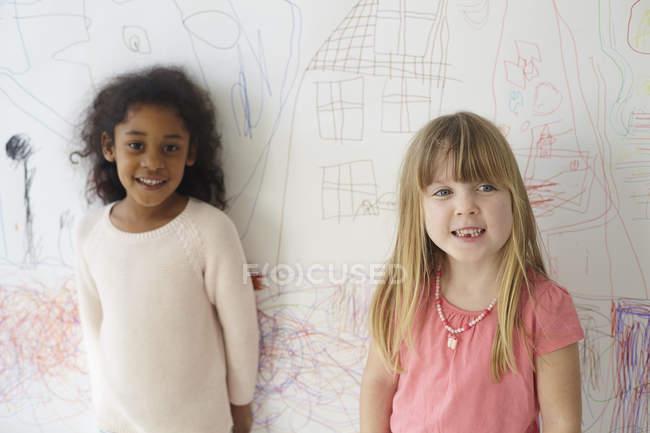 Retrato de niñas de pie contra el dibujo en la pared - foto de stock