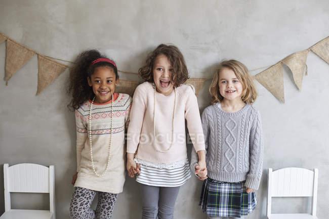 Amici sorridenti in piedi con le mani in mano contro il muro grigio decorato — Foto stock