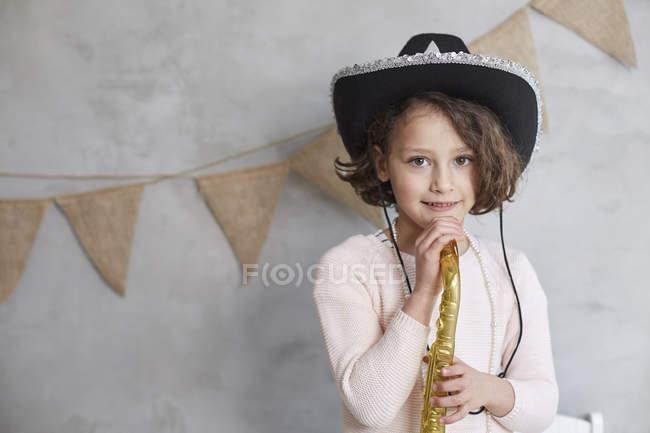 Портрет игривые девушки с Проп труба, стоя против оформлены стены — стоковое фото