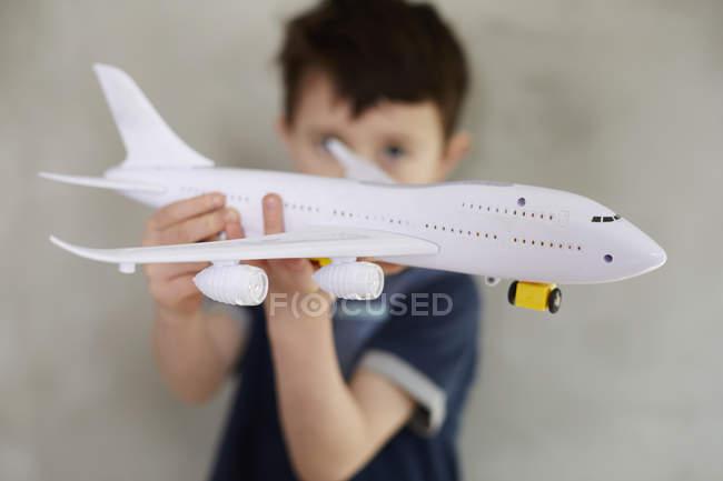 Мальчик играет с моделью самолета, стоя напротив серой стены — стоковое фото