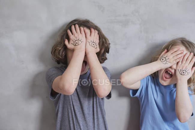 Verspielte Mädchen, die Augen mit bemalten Händen bedecken, während sie vor grauer Wand stehen — Stockfoto