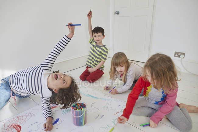Crianças brincalhões desenhando em papel enquanto sentadas no chão — Fotografia de Stock