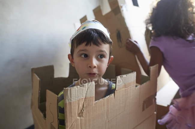 Мальчик в короне играет с картонными коробками от друга к стене — стоковое фото