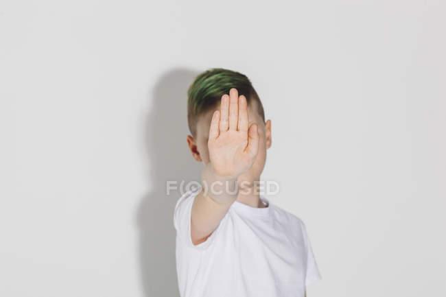 Menino mostrando sinal de parada enquanto está de pé contra fundo branco — Fotografia de Stock
