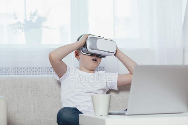 Menino vestindo fone de ouvido realidade virtual enquanto sentado no sofá em casa — Fotografia de Stock